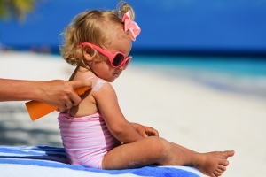 applying sunscreen to little girl baby